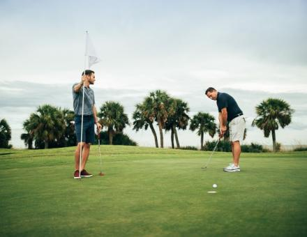 two men putting on green with palm trees in background
